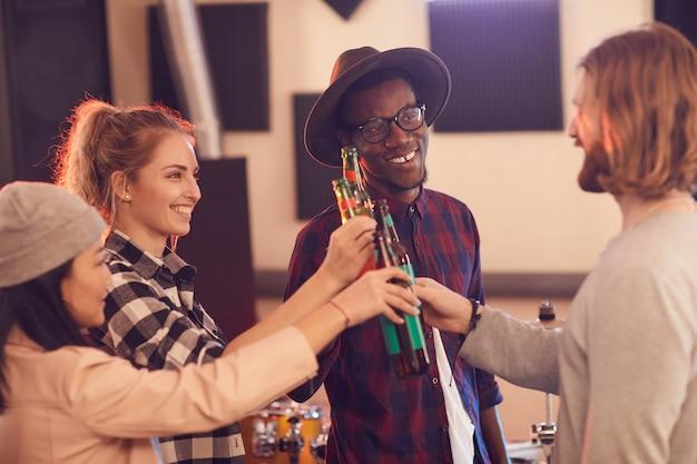 Groupe multiethnique de jeunes grillage avec des bouteilles de bière