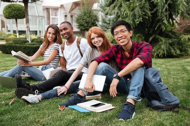 Groupe multiethnique de jeunes heureux lisant des livres sur la pelouse à l'extérieur