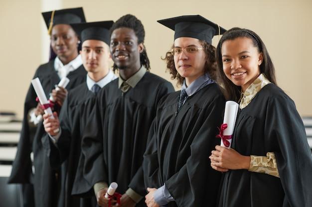 Groupe multiethnique de jeunes heureux portant des robes de graduation debout dans la rangée et regardant la caméra
