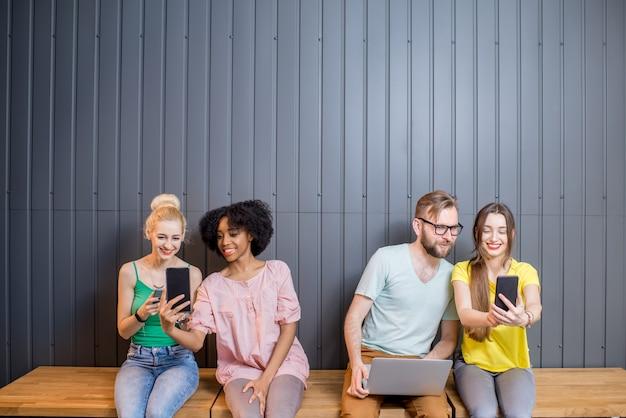 Groupe multiethnique de jeunes vêtus de t-shirts colorés discutant avec des gadgets assis dans une rangée à l'intérieur sur le fond du mur