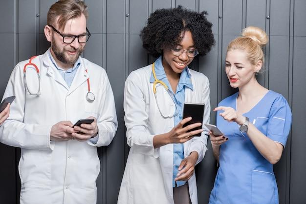 Groupe multiethnique de médecins s'amusant debout avec des téléphones sur fond de mur gris