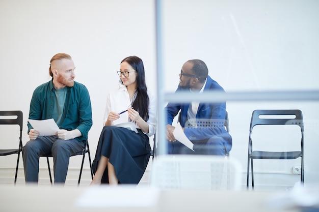 Groupe multiethnique de personnes faisant la queue pour un entretien d'embauche et bavardant derrière un mur de verre, copy space