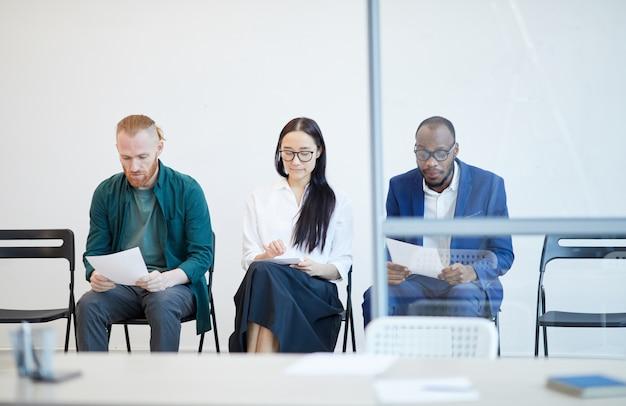 Groupe multiethnique de personnes faisant la queue pour un entretien d'embauche et tenant un cv derrière un mur de verre, copiez l'espace