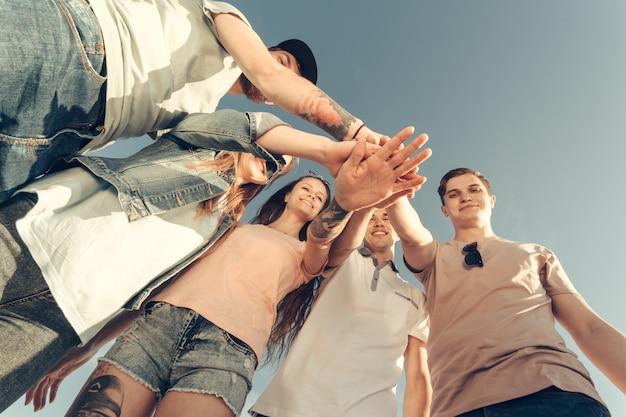 Groupe multiracial d'amis avec les mains sur la pile