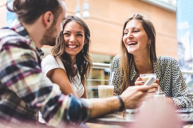 Groupe multiracial d'amis prenant un café ensemble