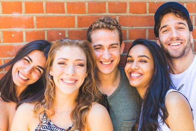 Groupe multiracial d'amis prenant un selfie ensemble