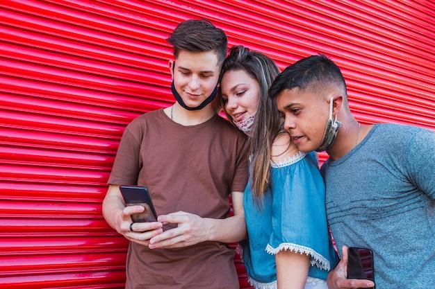 Groupe multiracial d'amis regardant un smartphone.
