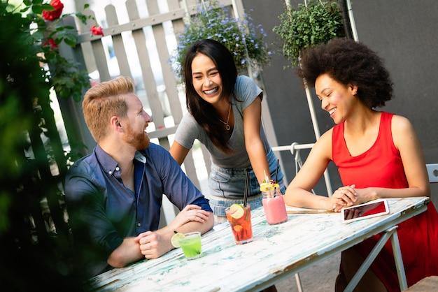Groupe multiracial d'amis s'amusant et parlant ensemble au café