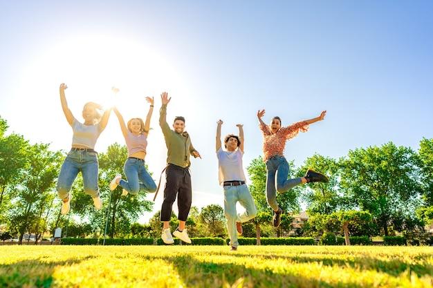 Groupe multiracial d'amis sautant haut avec les bras ouverts souriant