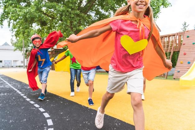 Groupe multiracial de jeunes écoliers portant des costumes de super-héros et s'amusant à l'extérieur