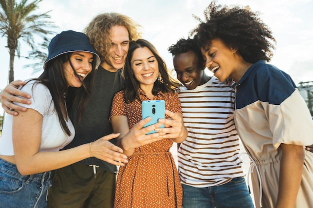 Groupe multiracial de jeunes regardant un smartphone en marchant dans la rue
