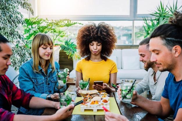 Groupe multiracial de personnes utilisant un téléphone intelligent mobile assis au bar-restaurant