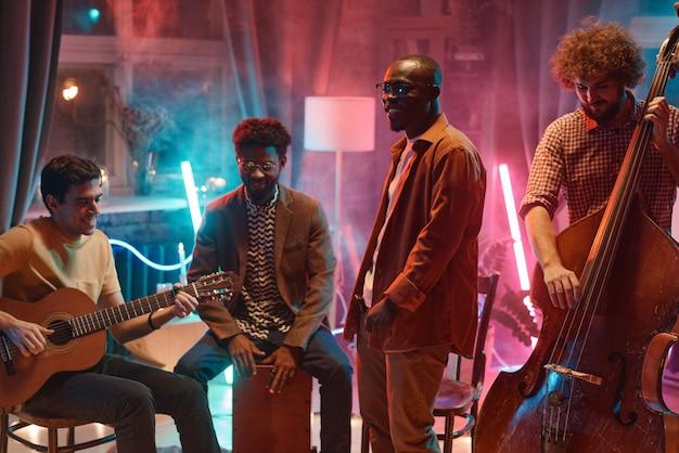 Groupe de musique jouant des instruments de musique qu'ils répètent en studio