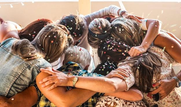 Un groupe de neuf femmes amicales s'embrassent et célèbrent la fête. les têtes pleines de confettis. concept de fête ou de carnaval