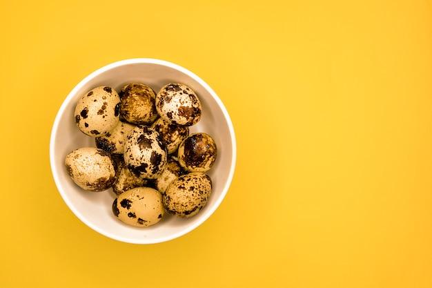 Groupe d'oeufs de caille en plaque blanche espace copie. vue de dessus. produits bio et sains. petits œufs crus frais naturels non cuits. petit déjeuner protéiné. régime céto.