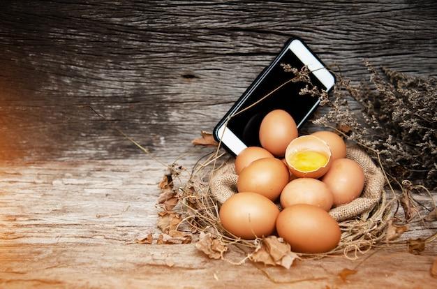 Groupe d'oeufs crus mis en face de téléphone portable, sur une planche en bois, ton clair et chaud
