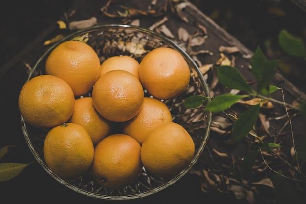 Groupe d'oranges fraîchement cueillies et section dans un panier