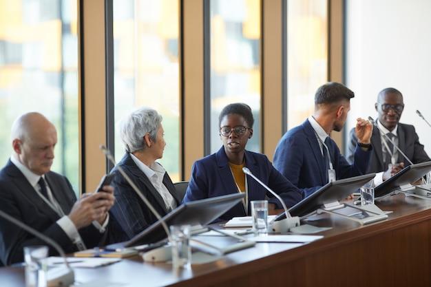 Groupe de partenaires commerciaux discutant des affaires ensemble au cours d'une conférence d'affaires au bureau