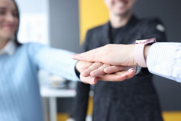 Groupe de partenaires pliant leurs mains ensemble en gros plan de bureau