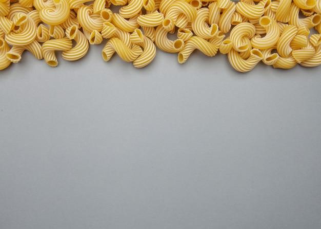 Groupe de pâtes macaroni sur fond gris