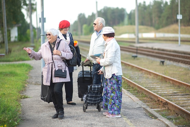 Groupe de personnes âgées âgées positives en attente de train avant de voyager
