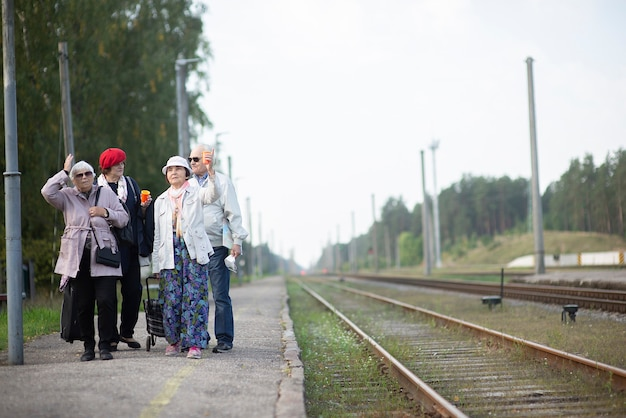 Groupe de personnes âgées âgées positives personnes âgées en attente de train avant de voyager