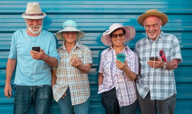 Groupe de personnes âgées en amitié debout contre un mur souriant et regardant le téléphone écoutant avec des écouteurs. visages joyeux et détendus pour le retraité