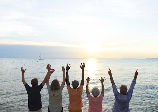 Groupe de personnes âgées bras levés sur la plage au coucher du soleil