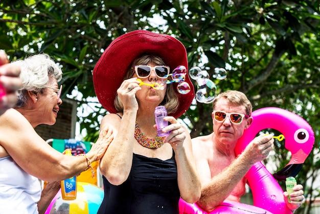 Groupe de personnes âgées diverses au bord de la piscine, soufflant des bulles de savon