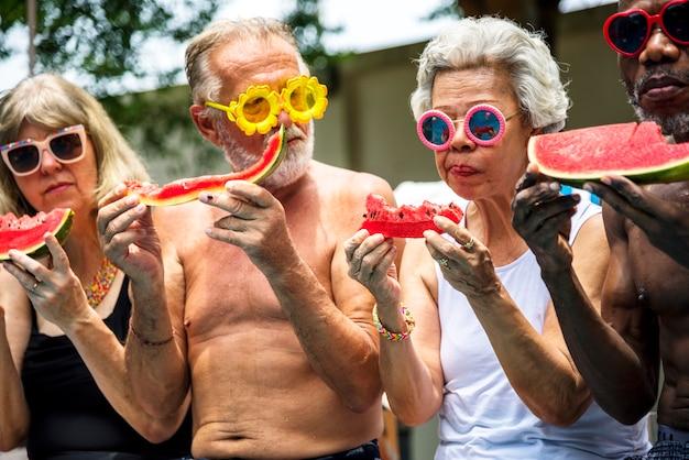 Groupe de personnes âgées diverses mangeant un melon d'eau ensemble