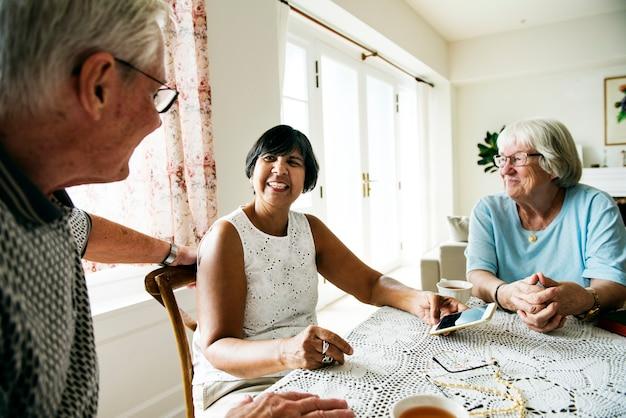 Groupe de personnes âgées diverses utilisant un téléphone mobile