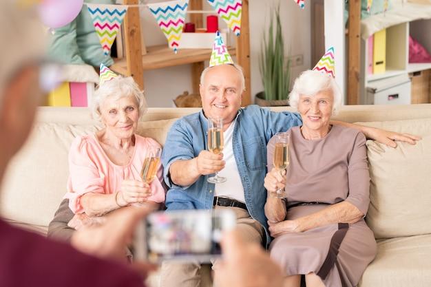 Groupe de personnes âgées de grillage pour anniversaire alors qu'il était assis sur un canapé à la maison