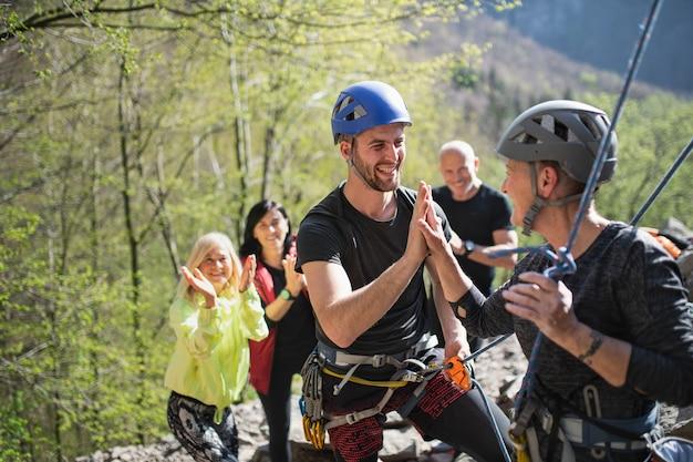 Un groupe de personnes âgées avec instructeur escalade des rochers à l'extérieur dans la nature, mode de vie actif.