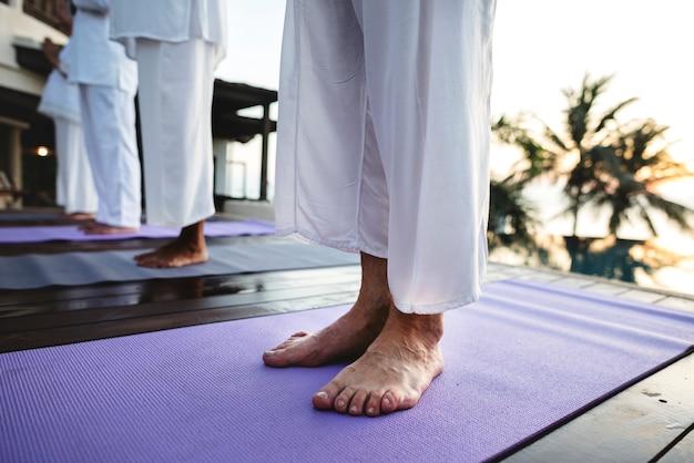 Groupe de personnes âgées pratiquant le yoga au bord de la piscine