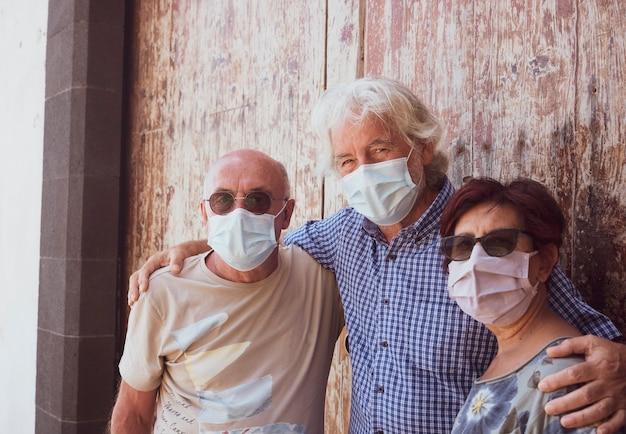 Groupe de personnes âgées sérieuses se tenant ensemble devant une vieille porte en bois portant un masque médical à cause du coronavirus - concept de nouvelle normalité