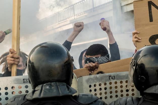 Groupe de personnes agressives avec des banderoles pour protester contre l'état tandis que la police anti-émeute les tient avec des boucliers dans une rue enfumée