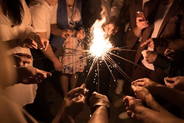 Groupe de personnes allumant les lumières du bengale ensemble. unité.