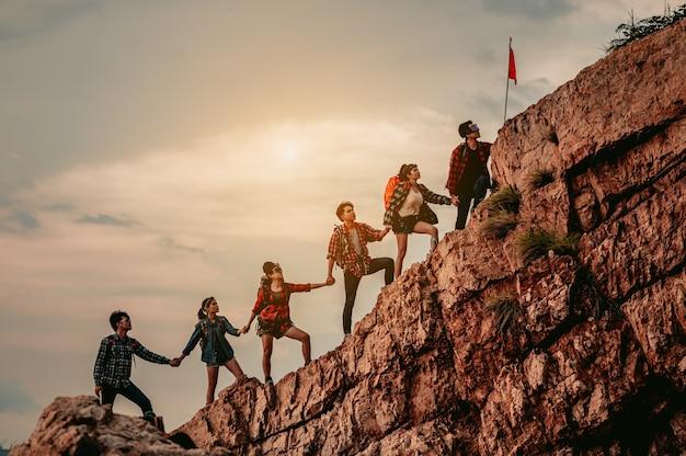 Groupe de personnes sur l'alpinisme de pointe aidant le travail d'équipe à réussir les voyages de trekking
