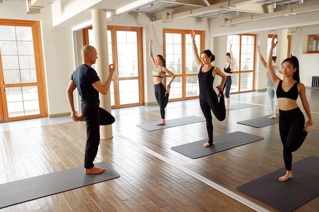 Groupe de personnes apprenant des cours de yoga dans un club de remise en forme. les étudiants s'exercent contre l'instructeur caucasien d'homme.