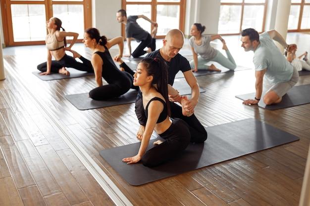 Groupe de personnes apprenant des cours de yoga dans un club de remise en forme. un instructeur caucasien entraîne et ajuste la pose correcte à une étudiante asiatique pendant que d'autres les suivent.