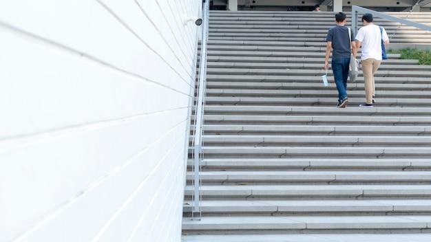 Un groupe de personnes à l'arrière monte dans le paysage d'escalier extérieur en béton.