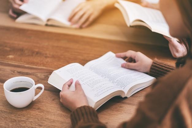 Groupe de personnes assises et appréciant de lire des livres ensemble sur une table en bois