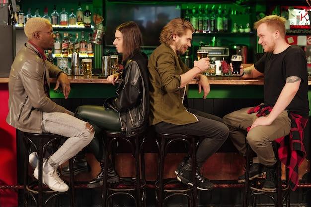 Groupe de personnes assises au comptoir du bar buvant de la bière et se parlant dans le pub