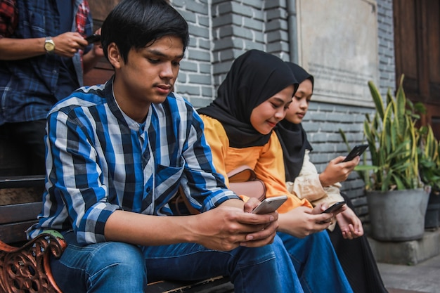 Groupe de personnes assises sur le banc et tapant sur un téléphone intelligent