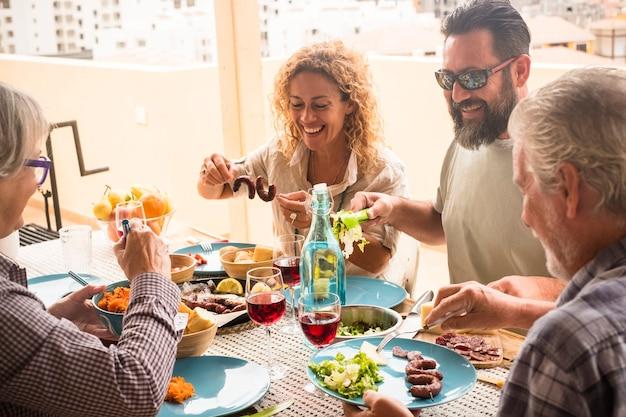Groupe de personnes assises à la maison avec une grande table pleine de nourriture et de boissons - concept familial en plein air en terrasse - fille, péché, grand-mère et grand-père s'amusent et mangent ensemble
