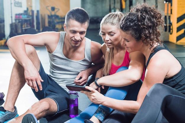 Groupe de personnes assises sur le sol à la recherche de smartphone dans la salle de gym