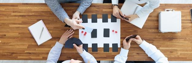 Groupe de personnes assises à table et jouant à des jeux de société vue de dessus concept de repos et de loisirs