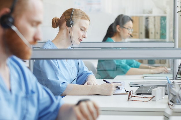 Groupe de personnes assises à la table et parler aux clients dans un centre d'appels médicaux