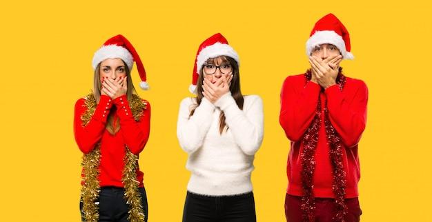Un groupe de personnes blonde femme habillée pour les vacances de noël couvrant la bouche