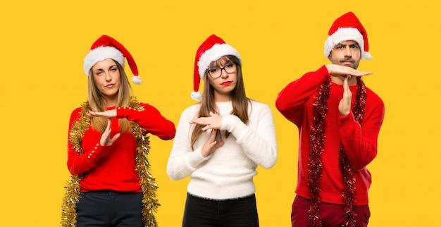 Un groupe de personnes blonde femme habillée pour les vacances de noël faisant un geste d'arrêt